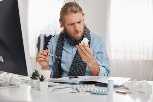 Ill bearded male office worker in blue shirt and scarf with spectacles concentrated on reading prescription of pills. young manager with flu, sits at workplace surrounded by drugs, tablets, vitamins