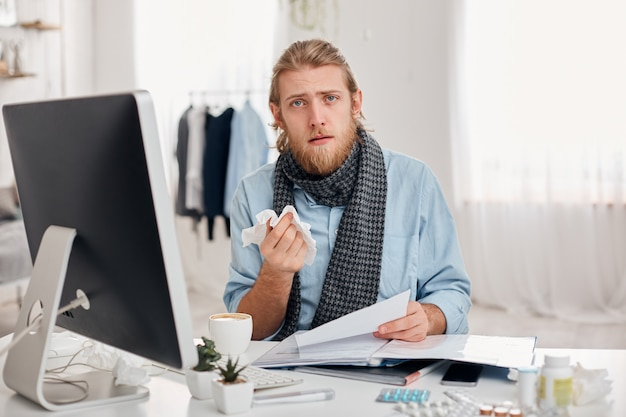 Ill bearded man sneezes, uses handkerchief, feels unwell, has flu. sick male office worker has fever and tired expression, discusses working issues with colleagues. illness and infection concept