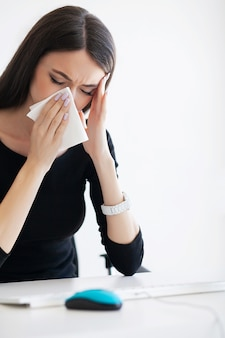 Ill business woman suffering at work behind the desk in her office and having allergy problem.