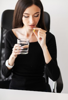 Ill businesswoman complaining and taking a pill at the office.