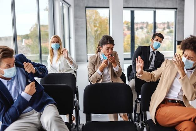 Больная бизнесвумен кашляет, сидя со своими коллегами на семинаре. коллеги боятся вируса короны, поэтому прячутся.