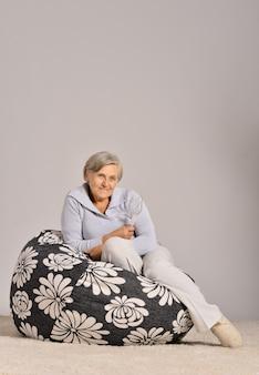 Ill elderly woman sitting in armchair on grey background