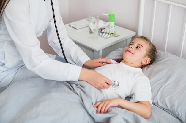 Ill girl being examined by the doctor