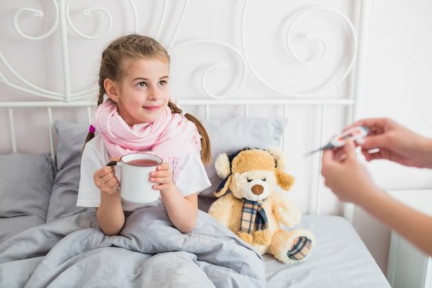 Ragazza malata usando il termometro