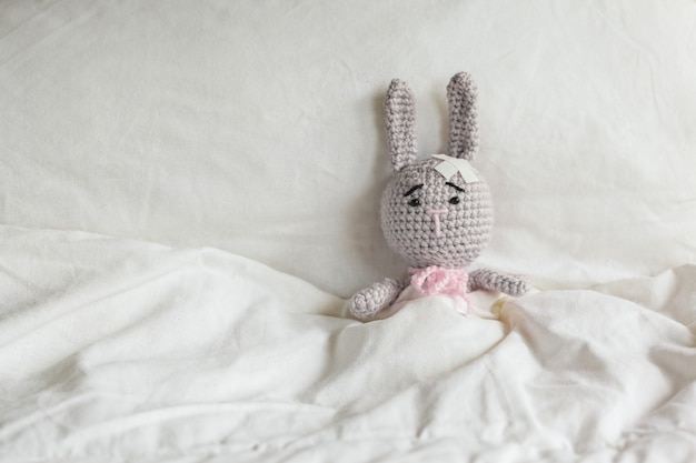 Ill grey toy rabbit with plaster on head in white bedroom.