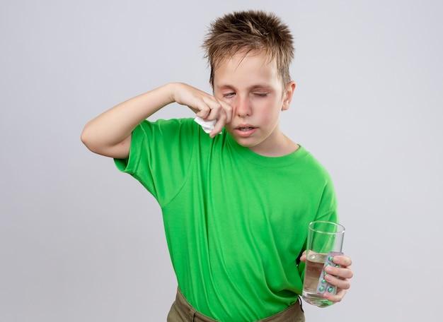 Ragazzino malato in maglietta verde sensazione di malessere tenendo un bicchiere di acqua e pillole asciugandosi il naso con un tovagliolo di carta che soffre di freddo in piedi sopra il muro bianco