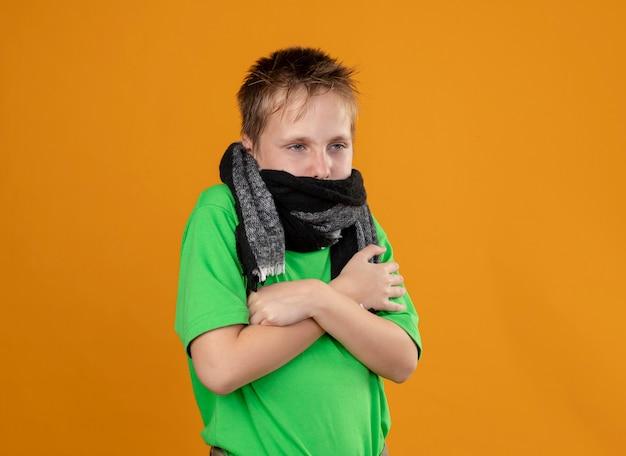 Ragazzino malato in maglietta verde e sciarpa calda intorno al collo e alla bocca che si sente male soffre di febbre e freddo in piedi sul muro arancione