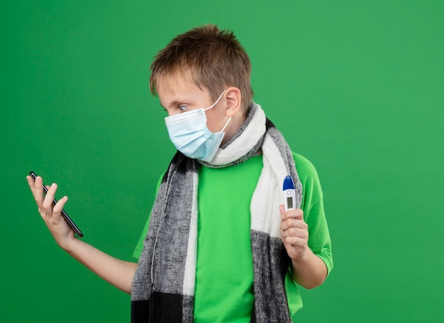 Ill little boy in green t-shirt and warm scarf around his neckwearing facial protective mask holding thremometer looking at his smartphone worried standing over green background