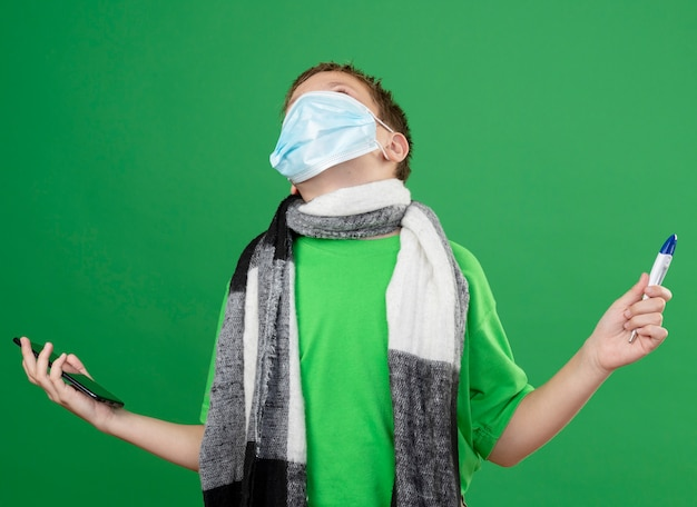 Ill little boy in green t-shirt and warm scarf around his neckwearing facial protective mask holding thremometer and smartphone looking frustrated standing over green background