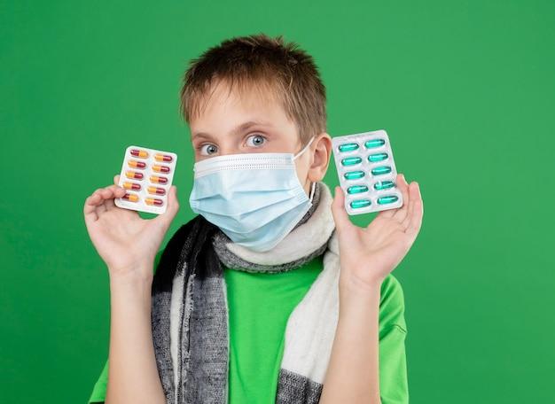 Ragazzino malato in maglietta verde e sciarpa calda intorno al suo collo maschera protettiva per il viso che mostra le pillole guardando la telecamera preoccupato in piedi su sfondo verde