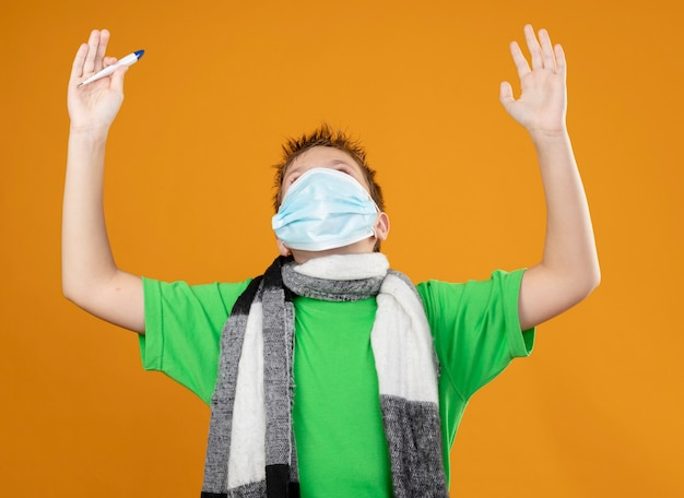 Больной маленький мальчик в зеленой футболке и теплом шарфе на шее, одетый в защитную маску для лица с термометром, глядя вверх с поднятыми руками, счастливый и взволнованный, стоящий над оранжевой стеной