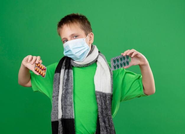 녹색 티셔츠와 녹색 배경 위에 서있는 카메라를보고 약을 보여주는 그의 neckwearing 얼굴 보호 마스크 주위에 따뜻한 스카프에 아픈 어린 소년