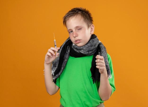 Больной маленький мальчик в зеленой футболке и теплом шарфе чувствует себя нездоровым, держа ампулу и шприц, несчастный и больной, стоящий над оранжевой стеной