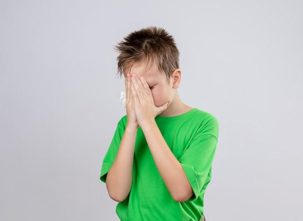 흰 벽 위에 서있는 손으로 얼굴을 덮고 몸이 좋지 않은 느낌의 녹색 티셔츠에 아픈 어린 소년