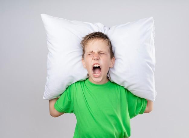 白い壁の上に立っているイライラした表情で叫んで枕を持って気分が悪い緑のtシャツの病気の小さな男の子