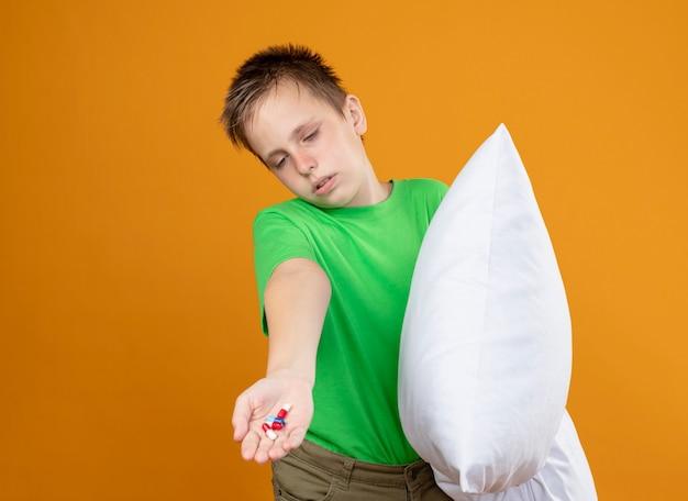 緑のtシャツを着た病気の少年は、枕を持って気分が悪くなり、オレンジ色の壁の上に立って混乱して不幸で病気になっているように見えます。