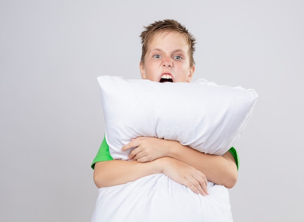 白い壁の上に立っている攻撃的な表情で叫んで枕を抱き締める気分が悪い緑のtシャツの病気の小さな男の子