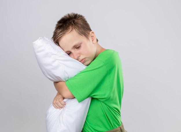 白い壁の上に立っている目を閉じて枕を抱き締める気分が悪い緑のtシャツの病気の小さな男の子