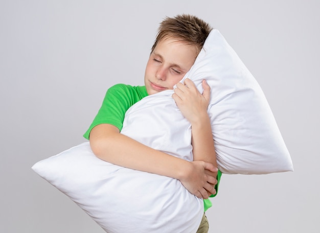 白い壁の上に目を閉じて枕を抱き締める気分が悪い緑のtシャツの病気の小さな男の子