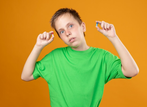 녹색 티셔츠에 아픈 어린 소년 오렌지 배경 위에 서있는 혼란스러워하는 카메라를보고 손에 알약을 보여주는 기분이 좋지 않습니다.