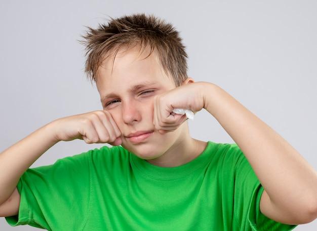 Больной маленький мальчик в зеленой футболке чувствует себя нездоровым, протирая глаза, стоя на белом фоне