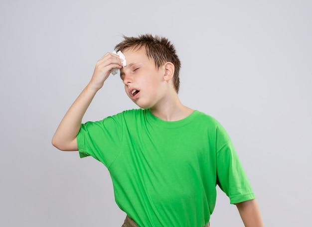 흰 벽 위에 서있는 종이 냅킨으로 그의 rorehead를 풀어주는 녹색 티셔츠 느낌의 아픈 어린 소년