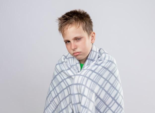 毛布に包まれた緑のtシャツを着た病気の少年は、白い壁の上に立って不幸で病気に見えて気分が悪い