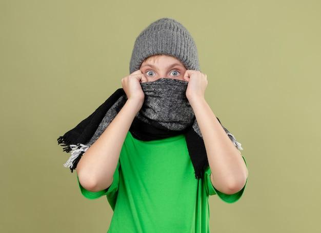 따뜻한 스카프와 스카프로 덮는 모자에 녹색 티셔츠를 입은 아픈 어린 소년 그의 얼굴은 가벼운 벽 위에 서있는 걱정을 찾고 있습니다.