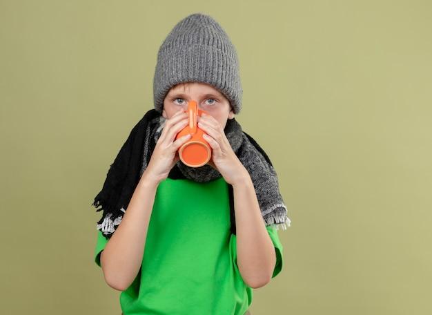 Больной маленький мальчик в зеленой футболке, теплом шарфе и шляпе пьет горячий чай, страдая от холода, стоя над светлой стеной