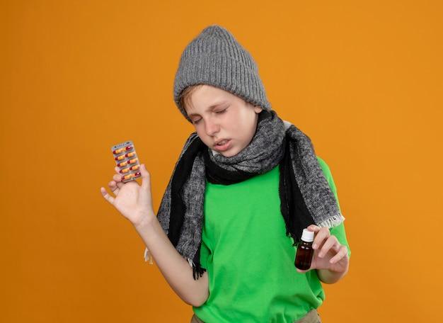 따뜻한 스카프와 모자에 녹색 티셔츠를 입고 아픈 어린 소년은 약 병과 약을 들고 아픈 느낌과 오렌지 벽 위에 서있는 불행한 약을 느낍니다.