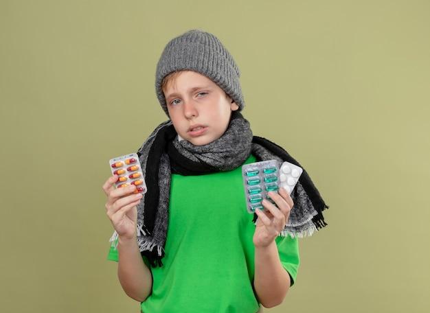 暖かいスカーフと帽子で緑のtシャツを着ている病気の小さな男の子は、軽い壁の上に立って不幸で病気の丸薬を持って気分が悪い