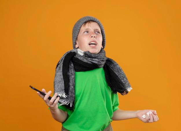 따뜻한 스카프와 모자에 녹색 티셔츠를 입고 아픈 어린 소년은 주황색 벽 위에 서서 혼란스럽고 불쾌한 서있는 스마트 폰과 종이 냅킨을 들고 불편 함을 느낍니다.