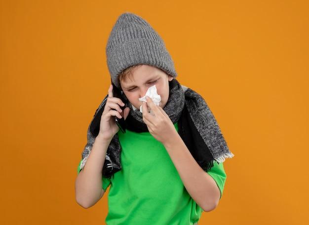 따뜻한 스카프와 모자에 녹색 티셔츠를 입고 아픈 어린 소년은 오렌지 벽 위에 서있는 종이 냅킨으로 코를 닦는 휴대 전화로 말하는 불편 함을 느낍니다.