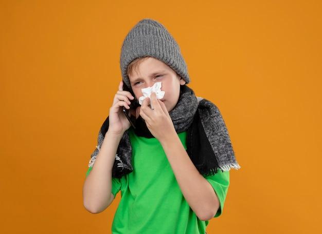 따뜻한 스카프와 모자에 녹색 티셔츠를 입고 아픈 어린 소년은 주황색 벽 위에 감기 서서 고통받는 종이 냅킨으로 코를 닦는 휴대 전화로 이야기하는 불편 함을 느낍니다.