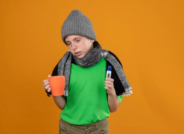 暖かいスカーフと帽子をかぶった緑色のtシャツを着て、熱いお茶と体温計を持った病気の少年