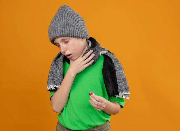 Больной маленький мальчик в зеленой футболке, теплом шарфе и шляпе с таблетками, плохо себя чувствует и кашляет, стоя у оранжевой стены