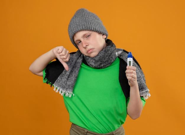 暖かいスカーフと帽子をかぶった緑色のtシャツを着て、体温計を持っている病気の少年は、オレンジ色の壁の上に立って親指を下に向けて気分が悪く、不幸に感じています
