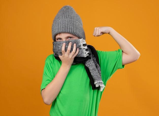 Больной маленький мальчик в зеленой футболке, теплом шарфе и шляпе, подняв кулак, чувствует себя лучше, стоя над оранжевой стеной