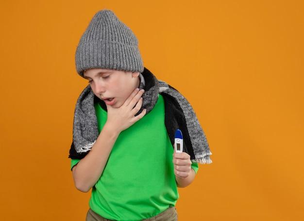 Больной маленький мальчик в зеленой футболке, теплом шарфе и шляпе, показывающий, что термометр плохо себя чувствует, больной и несчастный кашель стоит над оранжевой стеной