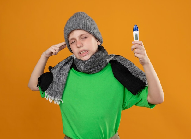 暖かいスカーフと帽子で緑のtシャツを着ている病気の少年は、温度計が気分が悪く、オレンジ色の背景の上に立っている寺院の近くでピストルのジェスチャーをして不幸に感じていることを示しています