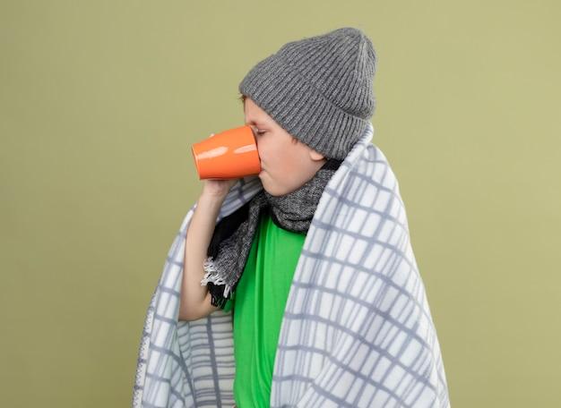 Больной маленький мальчик в зеленой футболке, теплом шарфе и шляпе, завернутой в одеяло, пьет горячий чай, страдает от холода, стоя над светлой стеной