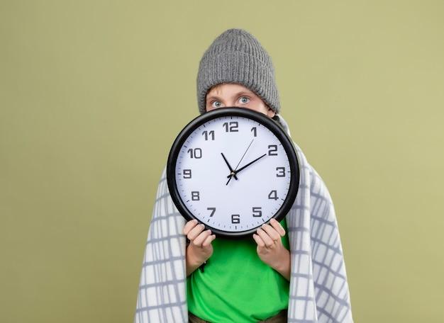 따뜻한 스카프와 모자에 녹색 티셔츠를 입고 아픈 어린 소년은 벽 시계를 들고 담요에 싸여 빛 벽 위에 서있는 시계 뒤에 얼굴을 방해