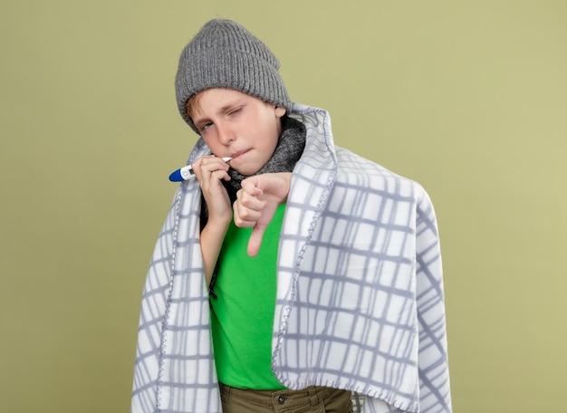 따뜻한 스카프와 모자에 녹색 티셔츠를 입고 아픈 어린 소년은 가벼운 벽 위에 서있는 엄지 손가락을 보여주는 온도를 측정하는 입에 온도계를 넣고 담요에 싸여 있습니다.