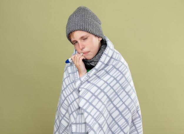 따뜻한 스카프와 모자에 녹색 티셔츠를 입고 아픈 어린 소년은 가벼운 벽 위에 서있는 온도를 측정하는 입에 온도계를 넣고 담요에 싸여 있습니다.