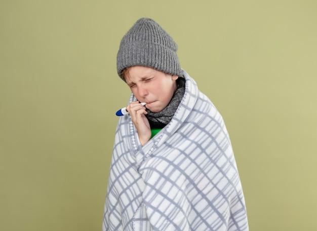 따뜻한 스카프와 모자에 녹색 티셔츠를 입고 아픈 어린 소년은 가벼운 벽 위에 서서 짜증나는 표정으로 온도를 측정하는 입에 온도계를 넣고 담요에 싸여 있습니다.