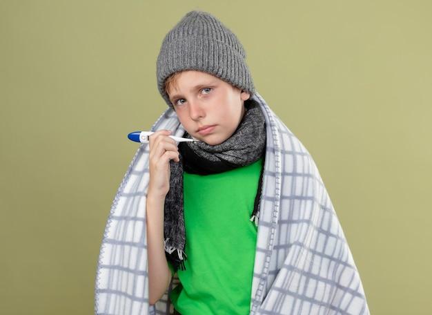 暖かいスカーフと帽子をかぶった緑のtシャツを着た病気の少年は、光の壁の上に立っている温度計が不幸で病気であることを示しています