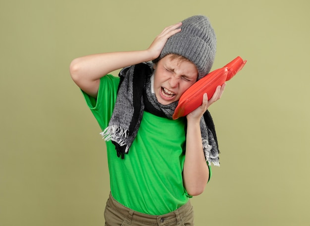 Ill little boy wearing green t-shirt in warm scarf and hat feeling unwell holding water bottle to keep warm suffering from strong headache standing over light wall