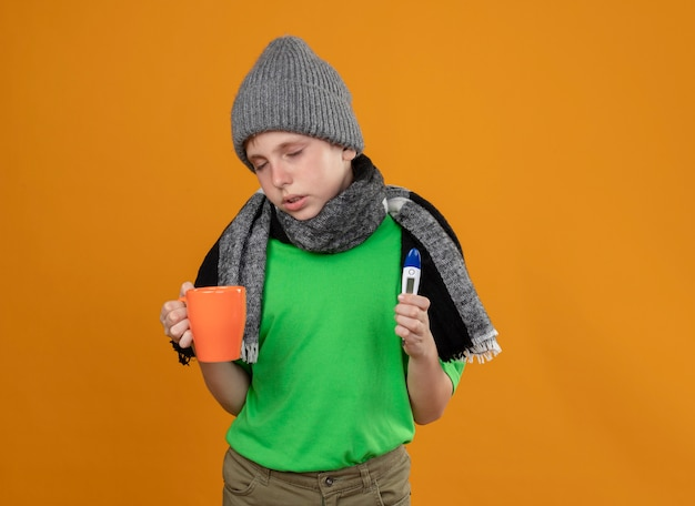 Ragazzino malato che indossa la maglietta verde in sciarpa calda e cappello che tiene tazza di tè caldo e termometro sensazione di malessere malato e infelice in piedi sopra la parete arancione