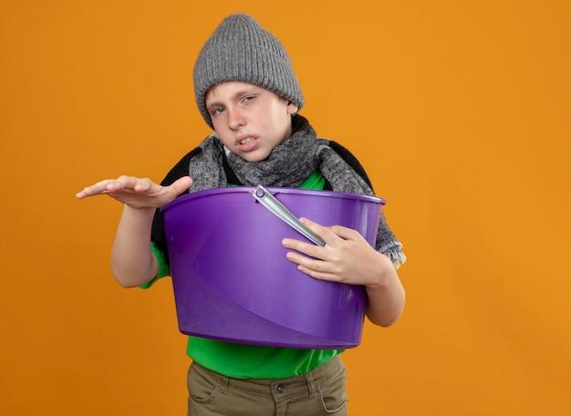 Ragazzino malato che indossa la maglietta verde in sciarpa calda e cappello che tiene la sensazione di nausea nel cestino in piedi sopra il muro arancione