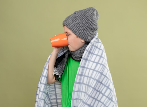 Ill little boy wearing green t-shirt in warm scarf and hat wrapped in blanket drinking hot tea suffering from cold standing over light wall